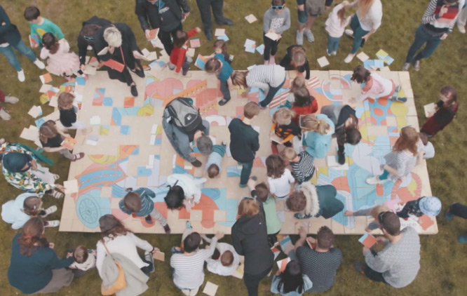 A group of people, mostly families and children sit outside on the grass creating a giant pastel coloured collage together.