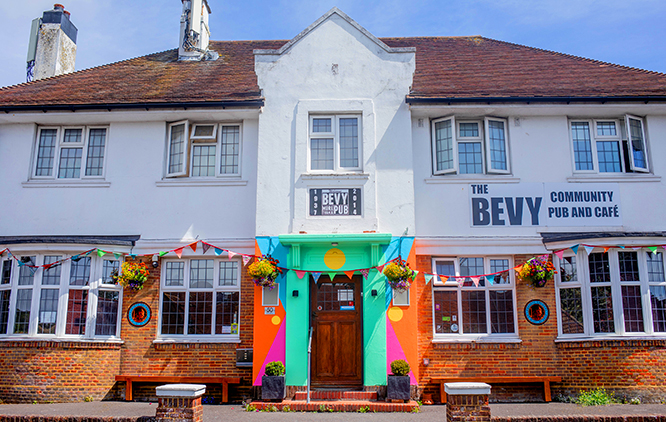 The Bevy is a pub, but also a community centre. In this image the sun is out and flags hang from above the main entrance. There are brightly coloured geometric shapes painted across the entrance.