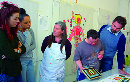 The Rocket Artists Brighton are pictured in their studio. There is a group of five individuals: two are looking at images and three are discussing the work separately. One is wearing an apron. On the wall is a large brightly coloured drawing of a figure and there are paintings all over the table in front of the group.