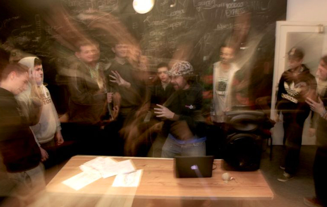The image of a group of young people rapping and making music in a dimly lit room.