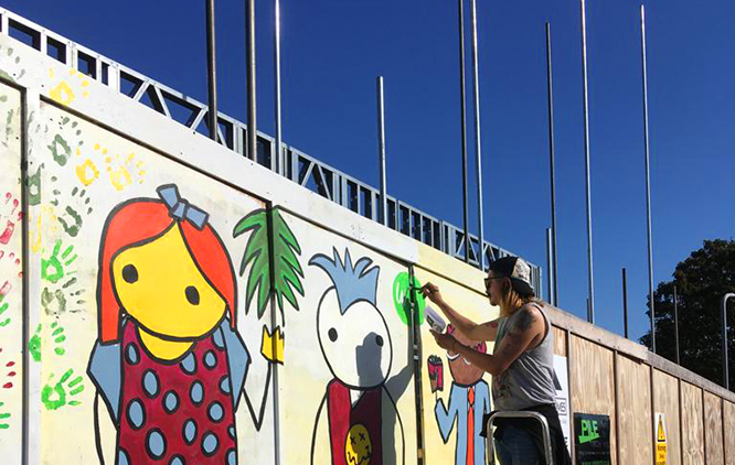 Image is of a blue sky and a person decorating a scaffold panel with illustrated characters.