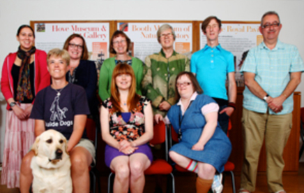 A group of individuals sit for the camera with a guidedog at the helm.