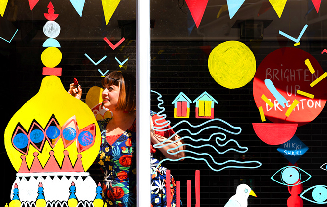 A person who may identify as female is illustrating a glass shop window with brightly coloured drawings of Brighton & Hove.