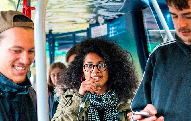 Image is of young people on a Brighton bus with mics