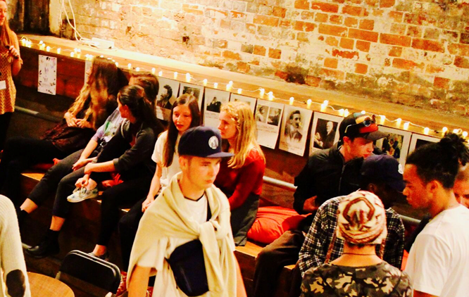 Image shows group of young people talking in a low lit room, in the Basement venue in Brighton. There is a brick wall behind them.