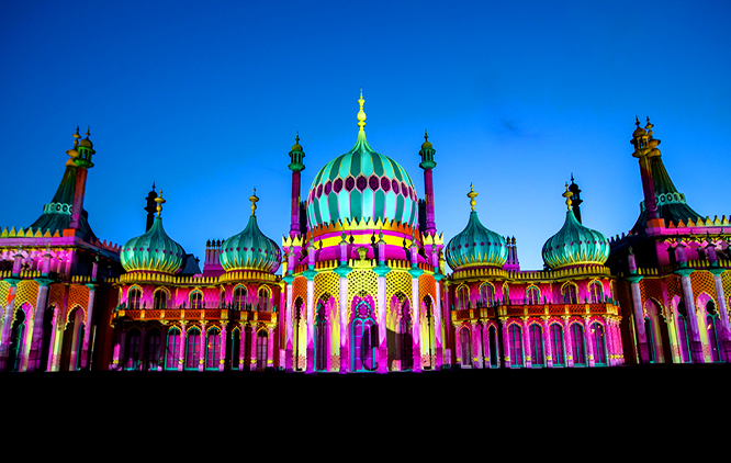 The image presents Brighton Dome at night, with colourful lighting projected on the front of the building.