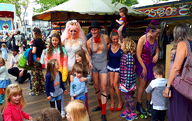 The image presents a group of circus performers of various ages in costumes and make-up, at what appears to be a festival. There are children around and several festival stands in the background.