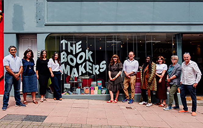 The image presents a group of people standing in front of a long shop window. The title on the window says: The Book Makers.