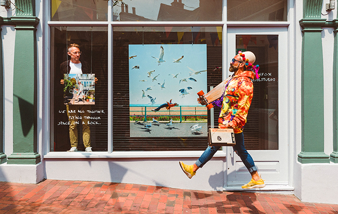 The image presents a green window frame on a street shop. Behind the window, on the left-hand side, a man is holding a picture. In the middle of the window, there is a large picture displayed presenting a seafront. In front of the window, there is a man in a colourful outfit floating in the air.