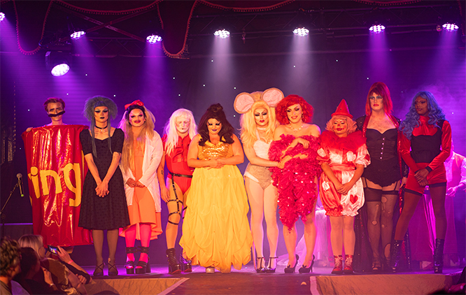 The image presents a group of people competing in a Drag pageant, standing on a stage. Contestants are wearing colourful clothing with the dominance of yellow and red. The background is lit by overhead lights which create a purple glow over the whole scene.